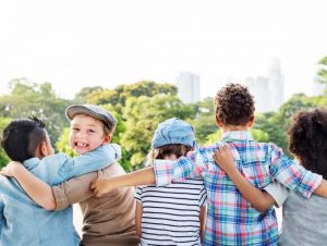 Kinder im Feriencamp sitzen lachend auf einer Mauer