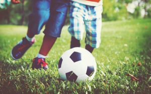 Kinder spielen Fußball auf dem Bolzplatz