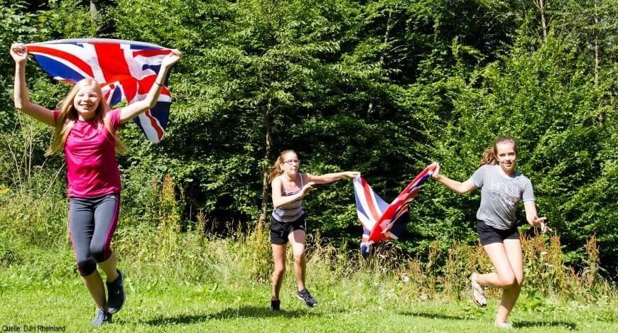 Englisch Adventure Feriencamp: Mädchen laufen mit England Flaggen