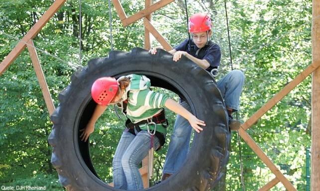 Englisch Adventure Feriencamp: Kinder klettern durch einen Riesenreifen