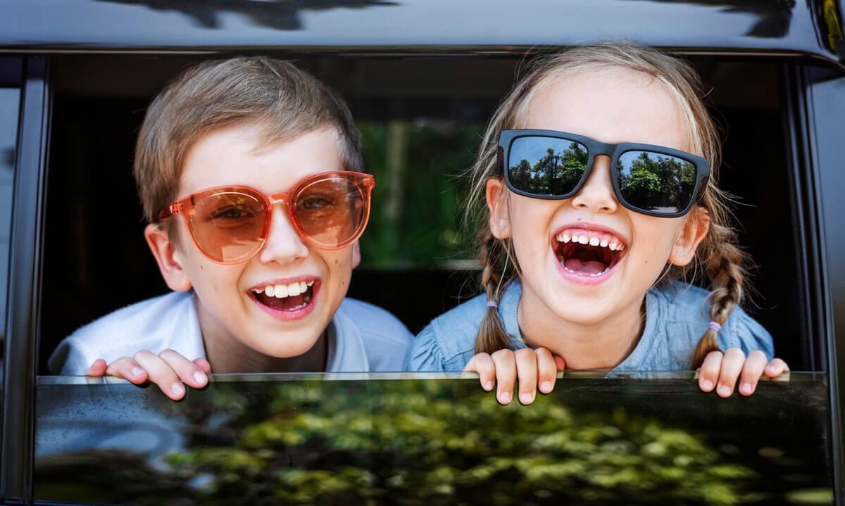 Kinder sitzend lachend im Auto